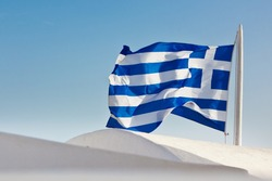 Close-up of a waving flag of Greece over the white round roofs of Santorini, Greece