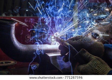 Close-up of a welder in protective gloves welds a metal pipe with a welding machine, blue sparks from welding scatter to the sides, a lot of smoke from welding
