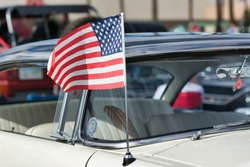 Close-up of a white and black classic American car with American flag on car antenna