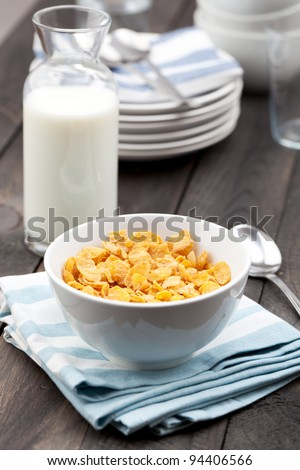 Close-up of a white bowl of cereal with a bottle of fresh milk. Served on a dark rustic wooden table, with a metal spoon on a napkin.