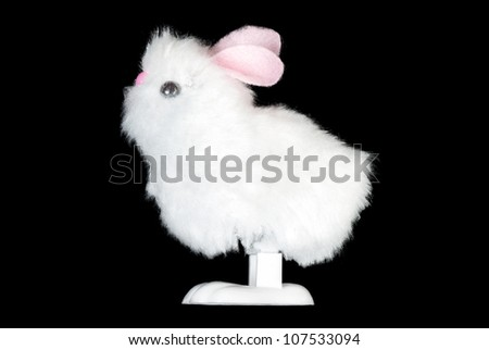 Close-up of a white fluffy bunny toy, side view.