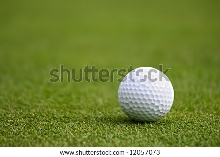 Close-up of a white golf ball on green.  Shallow focus. - stock photo