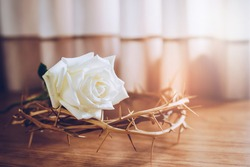 Close up of a white rose on the crucifix of Jesus Christ on top of wooden table background