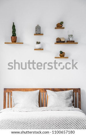 Close-up of a white wall with small decorations on shelves above a wooden headboard of a bed with pillows and blanket in a bright bedroom interior. Real photo. #1100657180