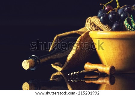Close up of a wine bottle and dark grapes in wooden basket, against black background. #215201992