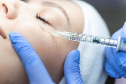 Close up of a woman being injected a dermal filler into the under-eye area by a cosmetician