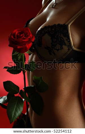 Close up of a woman body with a red rose on red background