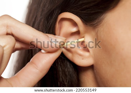 close-up of a woman cleans her ear with hygiene swab
