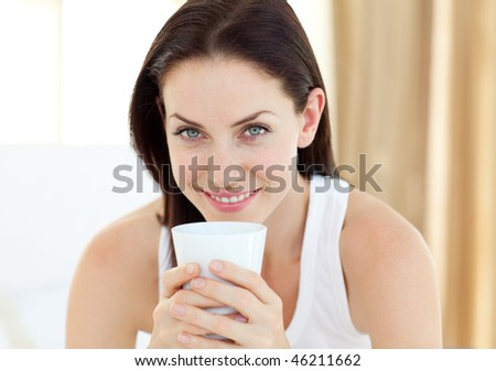 Close-up of a woman drinking a coffee sitting on her bed