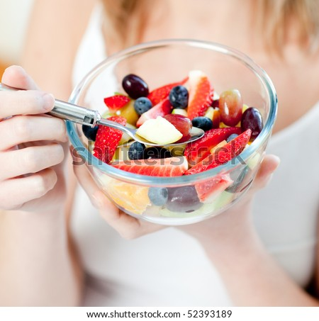 Close-up of a woman eating a fruit salad at home