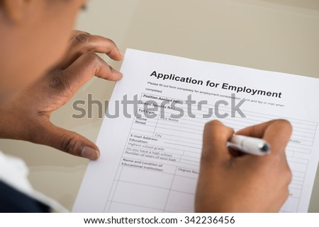 Close-up Of A Woman Filling Employment Form