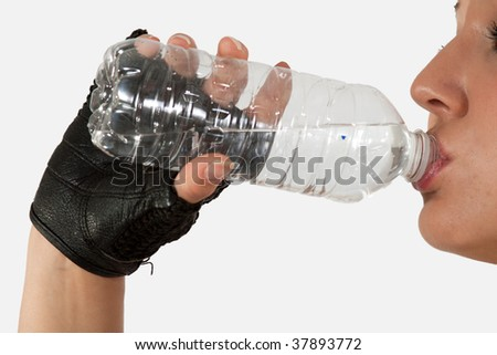 Close up of a woman hand holding and drinking from a clear water bottle