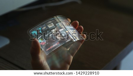 Close up of a woman hand is using a futuristic liquid crystals cell phone with the latest advanced augmented reality holographic technology. #1429228910