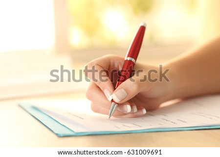 Close up of a woman hand using a pen to filling form on a table
