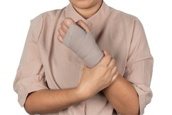 Close-up of a woman hand wrapping elastic bandage. Wounded hand cover with bandage. Medicine elastic bandage on woman hand isolated on white background.