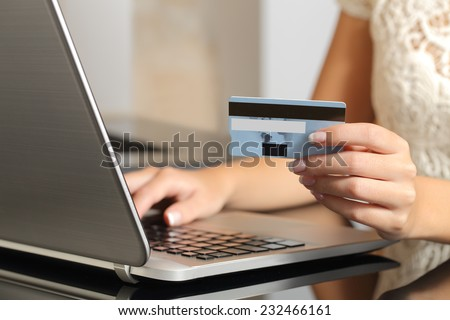 Close up of a woman hands buying online with a credit card and a laptop. Ecommerce concept