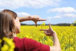 Close up of a woman hands framing flower in a yellow field in spring