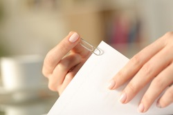 Close up of a woman hands putting a paper clip on a sheet at home