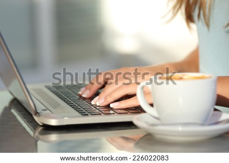 Close up of a woman hands typing in a laptop in a coffee shop terrace in the street stock photo