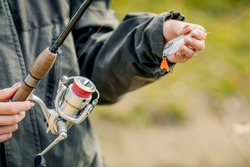 Close-up of a woman holding a fishing rod with a reel, sport fishing