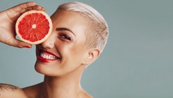 Close-up of a woman holding a grapefruit infront of her eye against grey background. Beautiful female model with short blond hair holding a grapefruit slice and smiling.