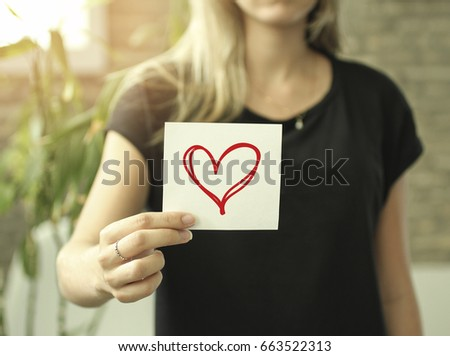 Close-up of a woman holding a paper with a heart drawn #663522313