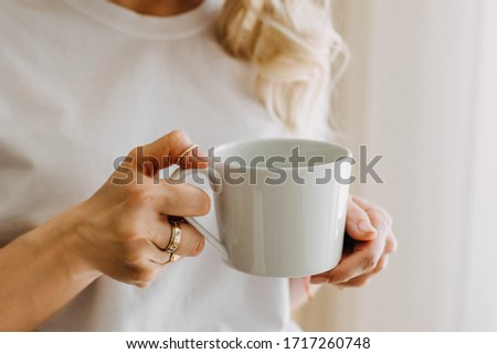 Close-up of a woman holding a white cup of coffee or tea. Foto stock ©