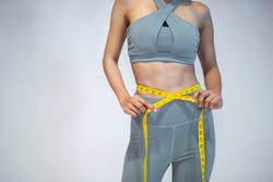 Close-up of a woman in sportswear measuring her waist after training at gym.