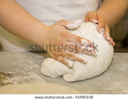 Close up of a woman kneading dough