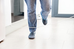 Close up of a woman legs stumbling with an electrical cord at kitchen