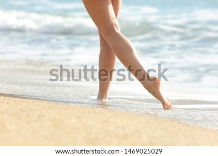 Close up of a woman legs walking on sea water on the beach