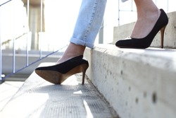 Close up of a woman legs with heels walking down stairs and spraining ankle