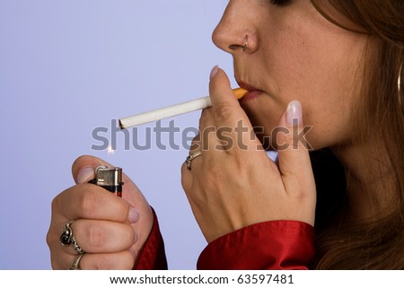 Close up of a woman lighting a cigarette with lighter