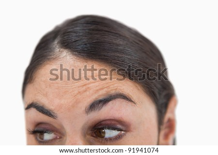 Close up of a woman looking under her against a white background