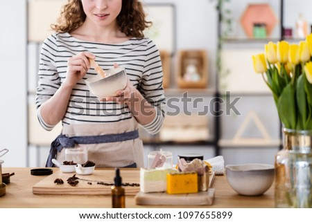 Close-up of a woman making organic face cream with chocolate in a bowl