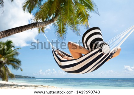 Close-up Of A Woman Relaxing On Striped Hammock Tied On Palm Tree At Idyllic Beach #1419690740