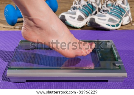 Close up of a woman's bare foot stepping on to a scale.
