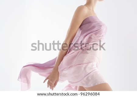 Close up of a woman\'s body wearing a floaty sarong.