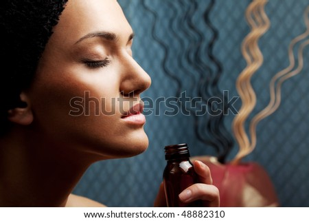 close-up of a woman's face, smelling aroma bottle