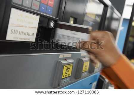 Close-up of a woman's hand doing transaction at petrol station
