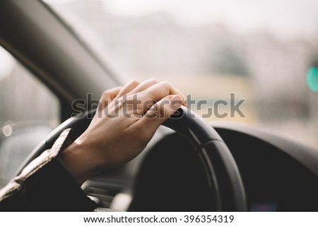 Close-up of a woman\'s hand driving a car