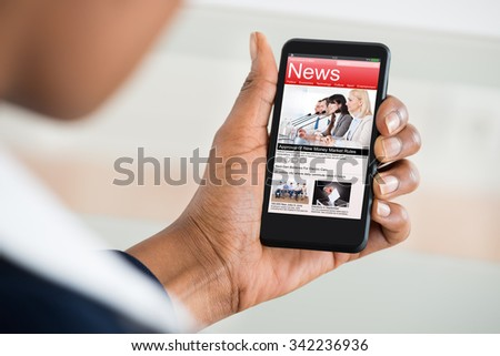 Close-up Of A Woman\'s Hand Reading News On Mobile Phone