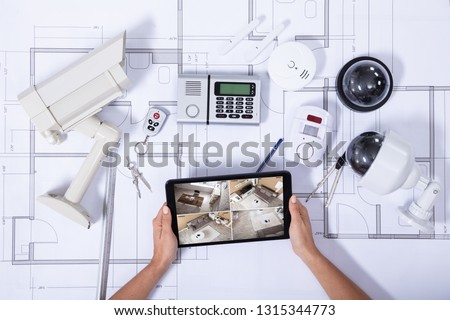 Close-up Of A Woman's Hand Using Digital Tablet For Monitoring CCTV Cameras Over The Blueprint