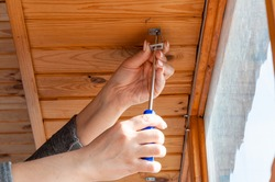 Close-up of a woman's hands holding a screwdriver, a woman installs metal brackets for attaching blinds to a wooden ceiling.