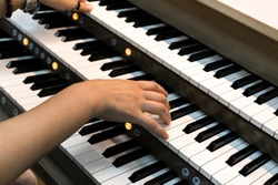 Close- up of a woman's hands playing a three-manual electronic organ.