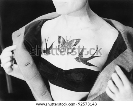 Close-up of a woman showing tattoos on her chest