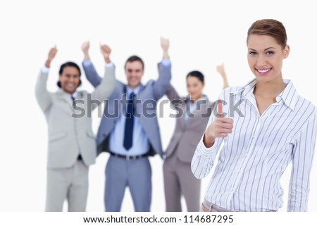 Close-up of a woman smiling and approving with enthusiastic business people with their thumbs up in background