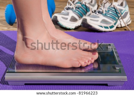 Close up of a woman standing barefoot on a scale.
