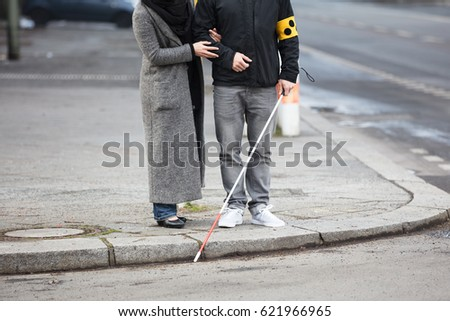 Close-up Of A Woman Standing With A Blind Man On Street #621966965