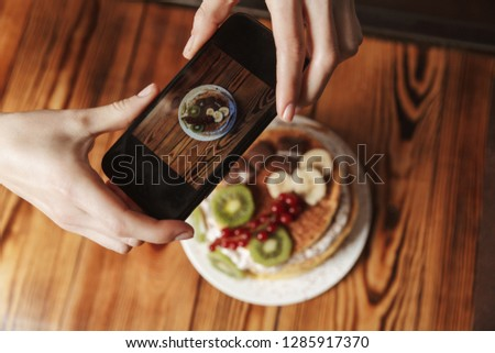 Close up of a woman taking a picture of pancakes with fruits and cream on a table